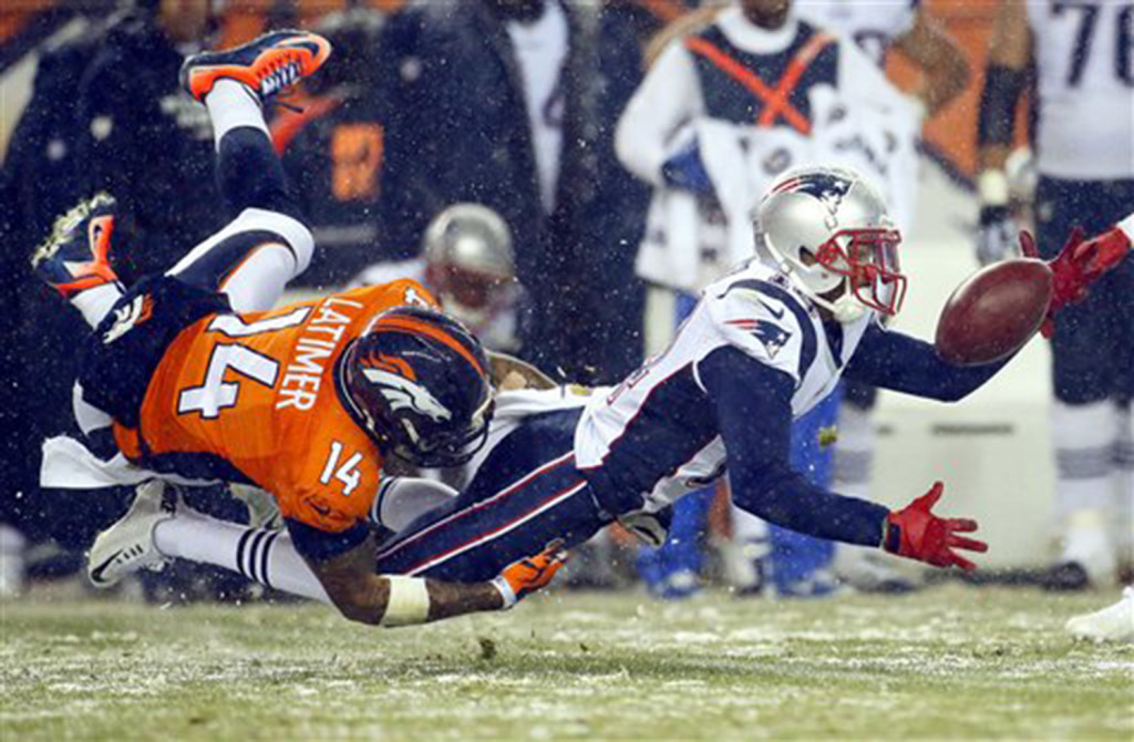Patriots wide receiver Chris Harper fumbles on a punt return as Broncos wide receiver Cody Latimer defends in the second half. The Associated Press