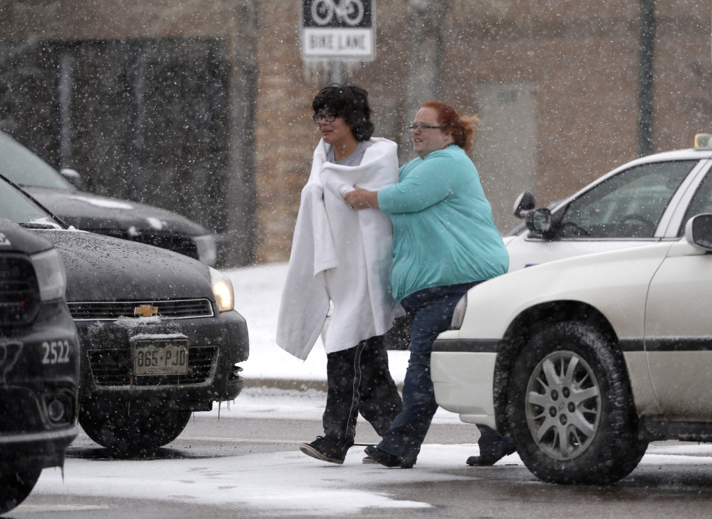 A person is escorted after reports of a shooting near the Planned Parenthood clinic in Colorado Springs, Colo.  Andy Cross/The Denver Post via AP