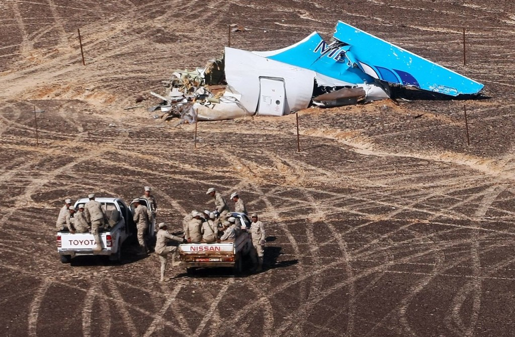 Egyptian military personnel approach the Metrojet plane's tail at the wreckage site in Hassana, Egypt, on Sunday. Russian Ministry for Emergency Situations via AP
