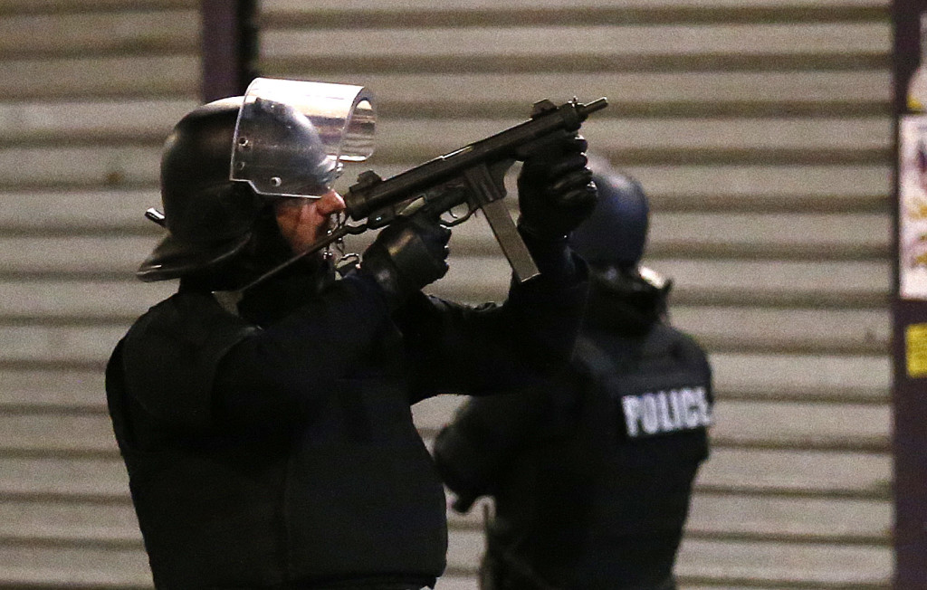 A police officer points his weapon during Wednesday morning's operation outside Paris. The Associated Press