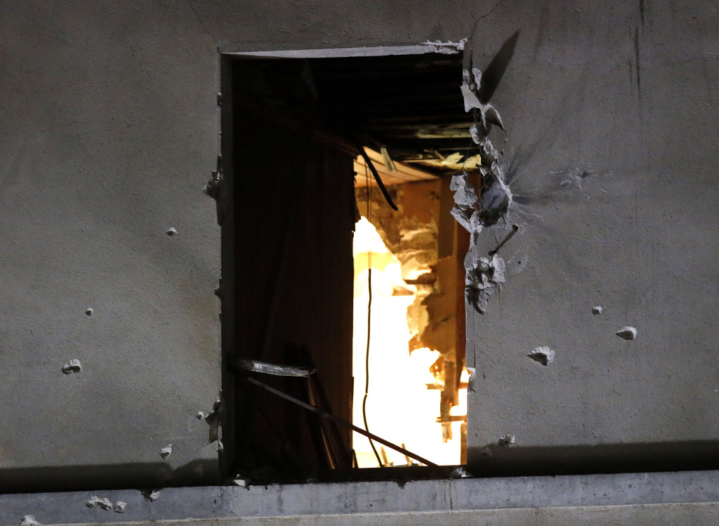 Bullet holes surround a window on the building that was raided early Wednesday in Saint-Denis, near Paris. A woman wearing an explosive suicide vest blew herself up as heavily armed police stormed the apartment where the suspected mastermind of last week's attacks was believed to be, police said. The Associated Press