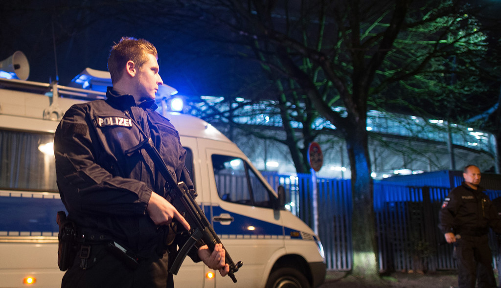 A police officer carries a submachine gun outside the HDI-Arena in Hanover, Germany, on Tuesday. The exhibition soccer match between Germany and Holland was canceled at short notice and the stadium was evacuated after a suspicious object was found.