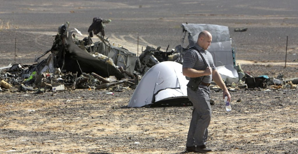 "A Russian investigator walks near wreckage a day after a passenger jet bound for St. Petersburg, Russia, crashed in Hassana, Egypt. The Russian passenger plane that crashed in Egypt was brought down by a homemade bomb placed on board in a ""terrorist"" act, the head of Russia's FSB security service told President Vladimir Putin on Tuesday. The Associated Press"