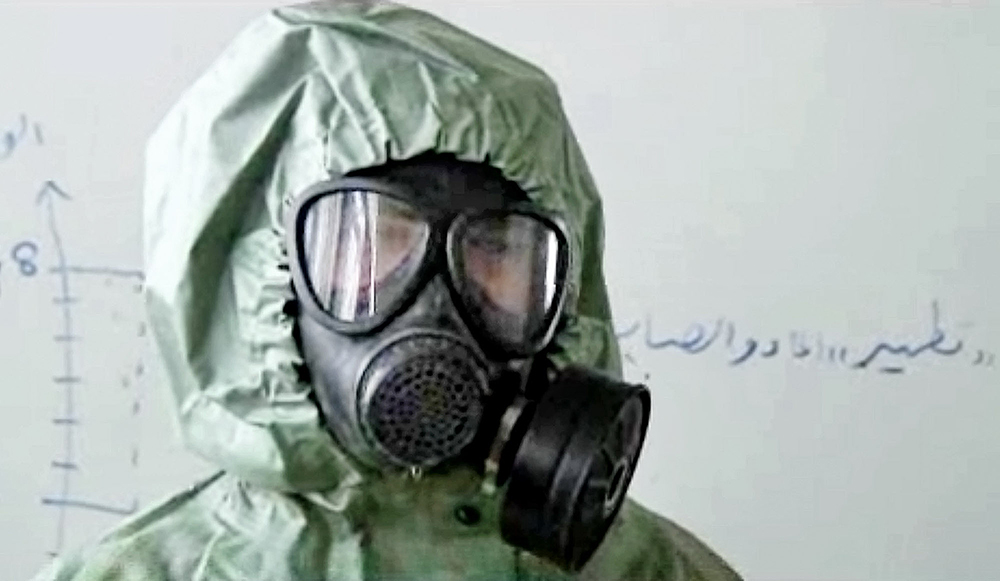 FILE - This image made from a September 2013 AP video shows a student wearing a gas mask and protective suit during a practice session on reacting  to a chemical weapons attack, in Aleppo, Syria. The Islamic State has set up a branch dedicated to chemical weapons research and experiments with the help of scientists from Iraq, Syria and elsewhere in the region, according to Iraqi and U.S. intelligence officials.