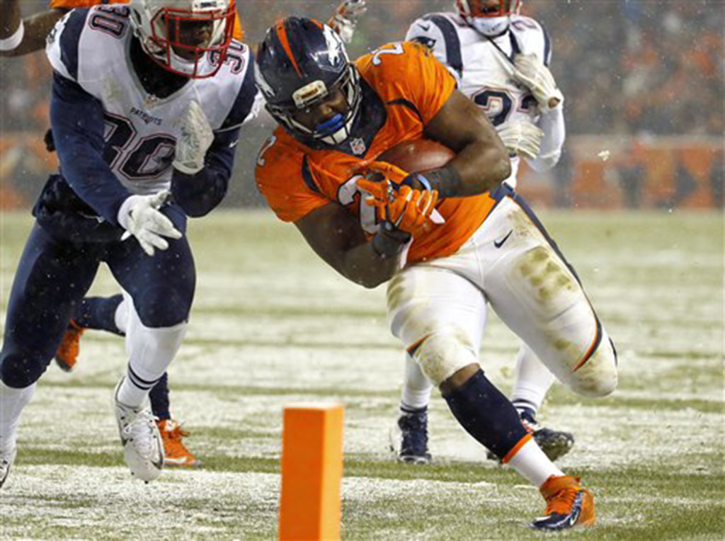 Broncos running back C.J. Anderson scores a touchdown as Patriots cornerback Duron Harmon defends in the second half. The Associated Press