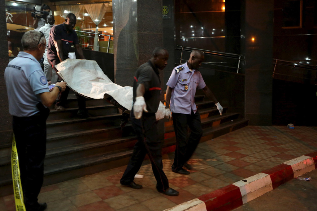 Malian officials carry a body outside the Radisson hotel after gunmen stormed the building in Bamako, Mali, on Friday.