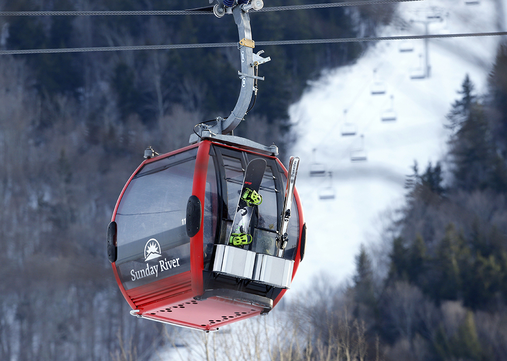 A snowboarder and skier ride the Chondola ski lift at Sunday River in Newry in this March photo. Sunday River is already open seven days a week for the season. An Oct. 19 opening earlier this fall was its third earliest opening in the resort's 56-year history. The Associated Press