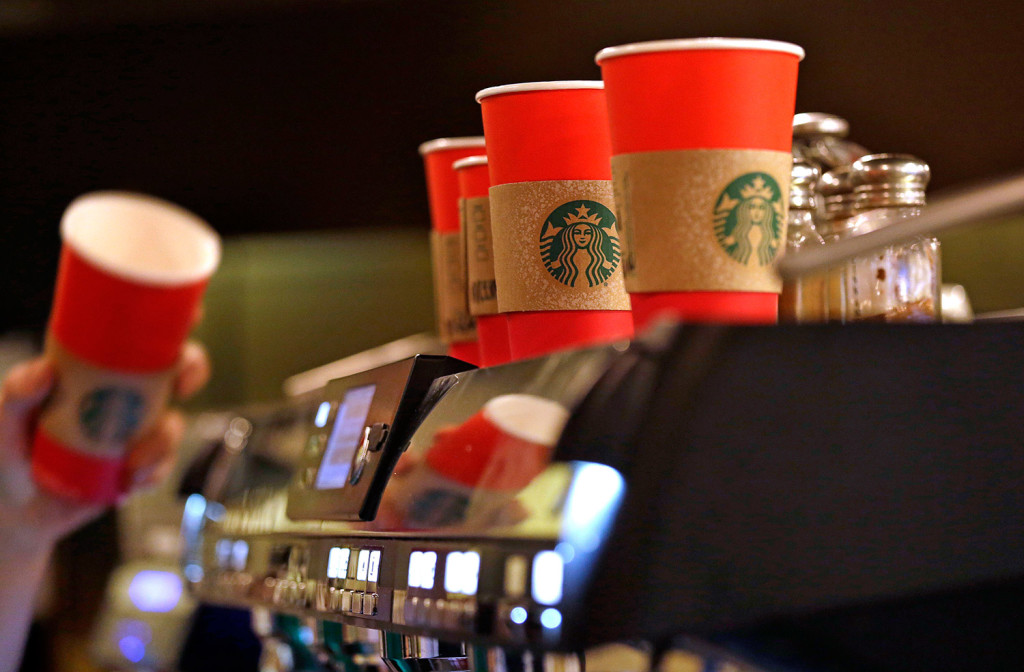 A barista reaches for a red paper cup as more, with cardboard sleeves attached, line the top of an espresso machine at a Starbucks coffee shop in Seattle. Starbucks' minimalist new holiday coffee cup has set off complaints that the chain is making war on Christmas.