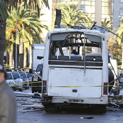 A man walks past the bus that exploded Tuesday in Tunis, Tunisia's president declared a 30-day state of emergency across the country and imposed an overnight curfew for the capital Tuesday after an explosion struck a bus carrying members of the presidential guard. The Associated Press
