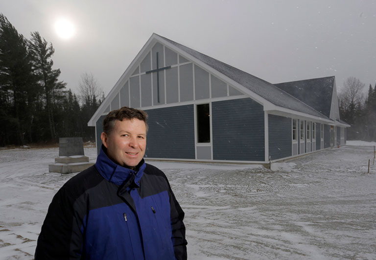 The Rev. Kevin Martin outside the new Catholic church in his northern Maine parish. The church will open its doors to his congregation 10 days before Christmas. Gabe Souza / Staff Photographer