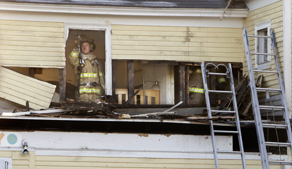 A firefighter checks for hot spots on the second floor of The Yellow House in Kennebunk on Friday. A fire broke out early Friday morning in the building that houses The Sugar Shack, PJ's Unique Peek and Ryan's Corner House, an Irish pub. Gregory Rec/Staff Photographer