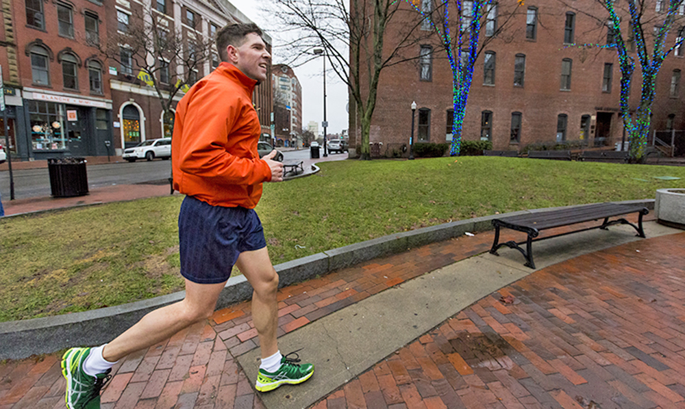 John Marshall, a visitor from Salem, New Hampshire, jogs in his shorts Thursday past the holiday lights in Tommy's Park on Exchange Street. Ben McCanna/Staff Photographer
