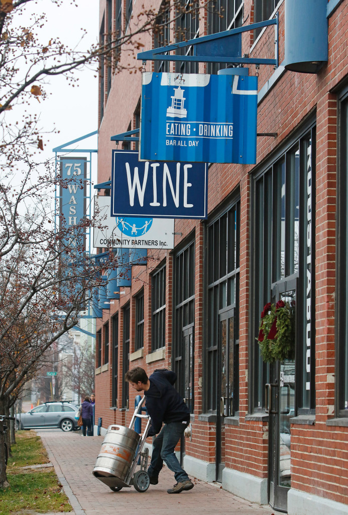 A delivery man brings a keg to Maine & Loire wine shop.  As the Old Port gets saturated, restaurants and food businesses are moving to the strip of Washington Avenue between Congress and Fox streets.