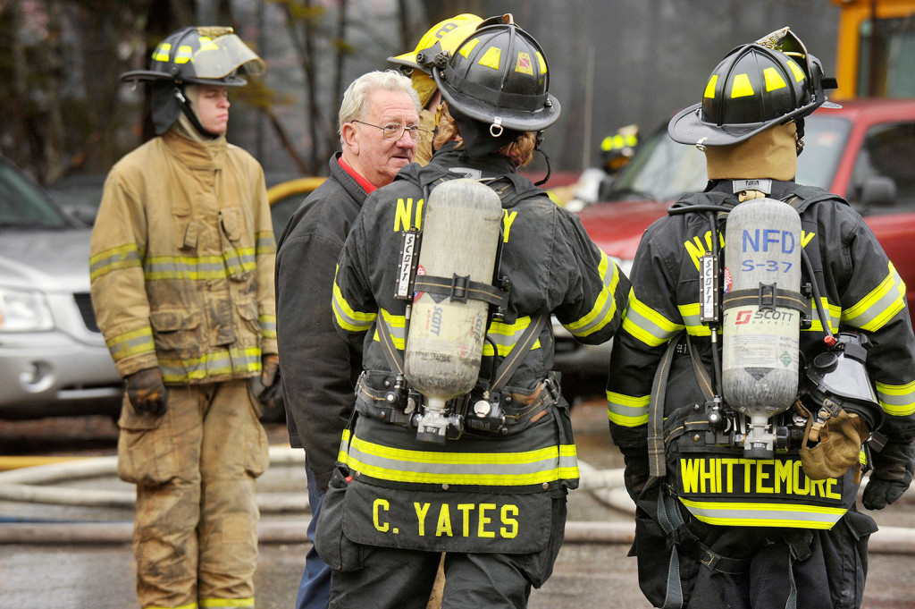 Ovide Corbiel, the owner of Ovide's Used Cars Inc., talks with firefighters at his business, which was destroyed by a fire Thursday. John Ewing/Staff Photographer