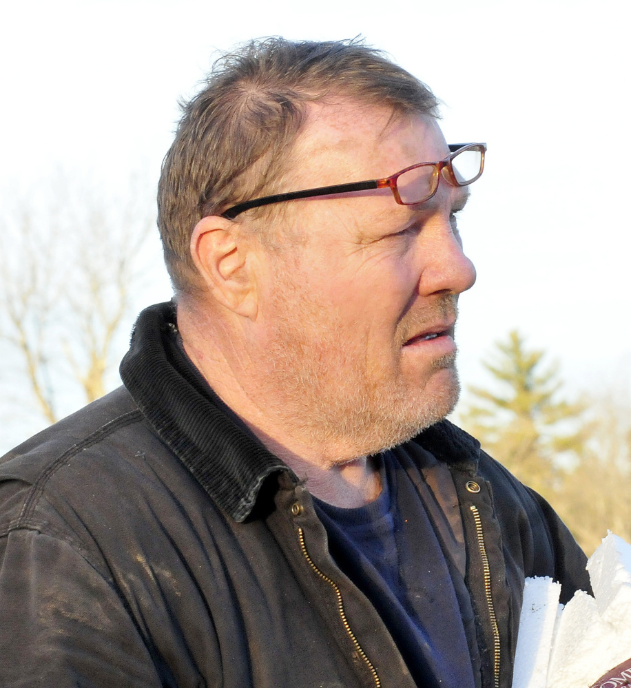 "Bob Somes watches as police investigate a fatal two-car accident near his home on Route 27 in Sidney on Sunday. Somes was at the scene where one vehicle flipped over in a ravine and people removed an injured boy before the car erupted in flames with the woman driver inside, according to Somes. ""The car exploded 20 seconds after the boy was removed,"" Somes said."