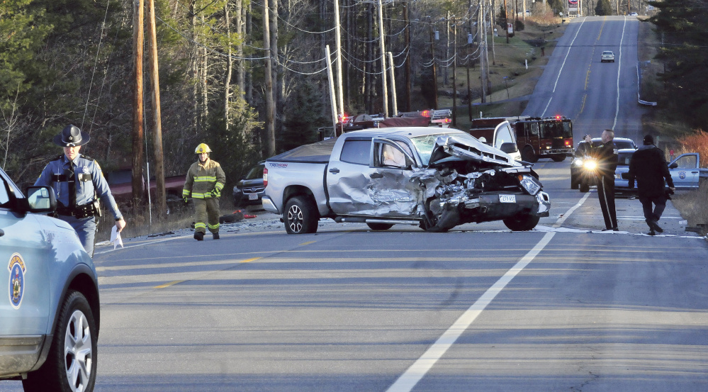 Police and firefighters investigate the scene of a fatal two-vehicle accident on Route 27 in Sidney on Sunday afternoon. This pickup truck and a vehicle that rolled over in a nearby ditch were involved. Bystanders removed an injured boy from the car before it erupted in flames, with a person inside.