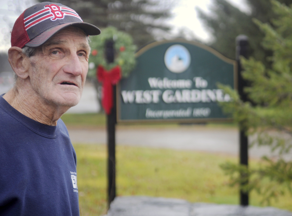 West Gardiner Selectman Mert Hickey stands at the town's welcome sign on Thursday at the border with Gardiner. Three of the town's welcome signs have been stolen.