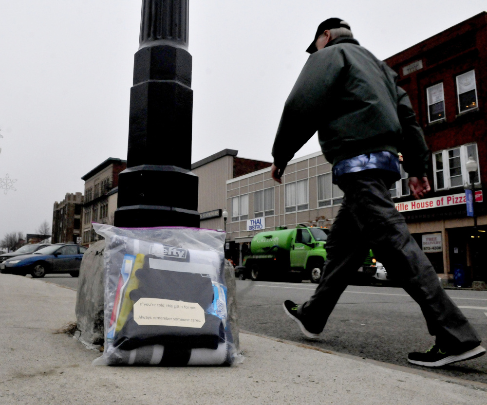 """A pedestrian walks past a care package containing a blanket, snacks and toiletries on Main Street in Waterville on Monday.  The note on package says, """"If you are cold this gift is for you. Always remember that someone cares."""""""