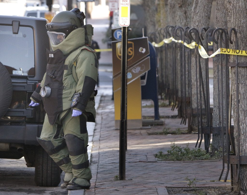 A member of the Portland police bomb squad returns to Middle Street while investigating a suspicious package that was found at 100 Middle St. on Monday. Police Chief Michael Sauschuck said police cleared the package from the building, which houses the FBI regional office and the U.S. Attorney's Office.  Gregory Rec/Staff Photographer