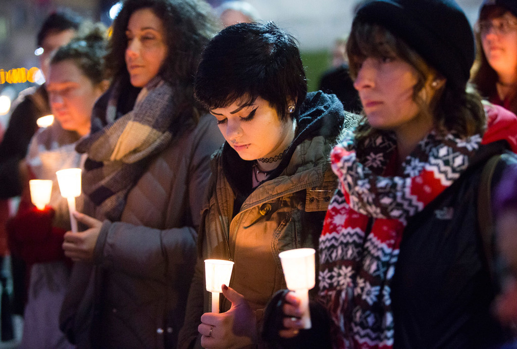 Shannon O'Connor of Portland bows her head during Tuesday's vigil, joined by Awapuhi Dancil of Cape Elizabeth, left, and Alex King of Portland. Carl D. Walsh/Staff Photographer