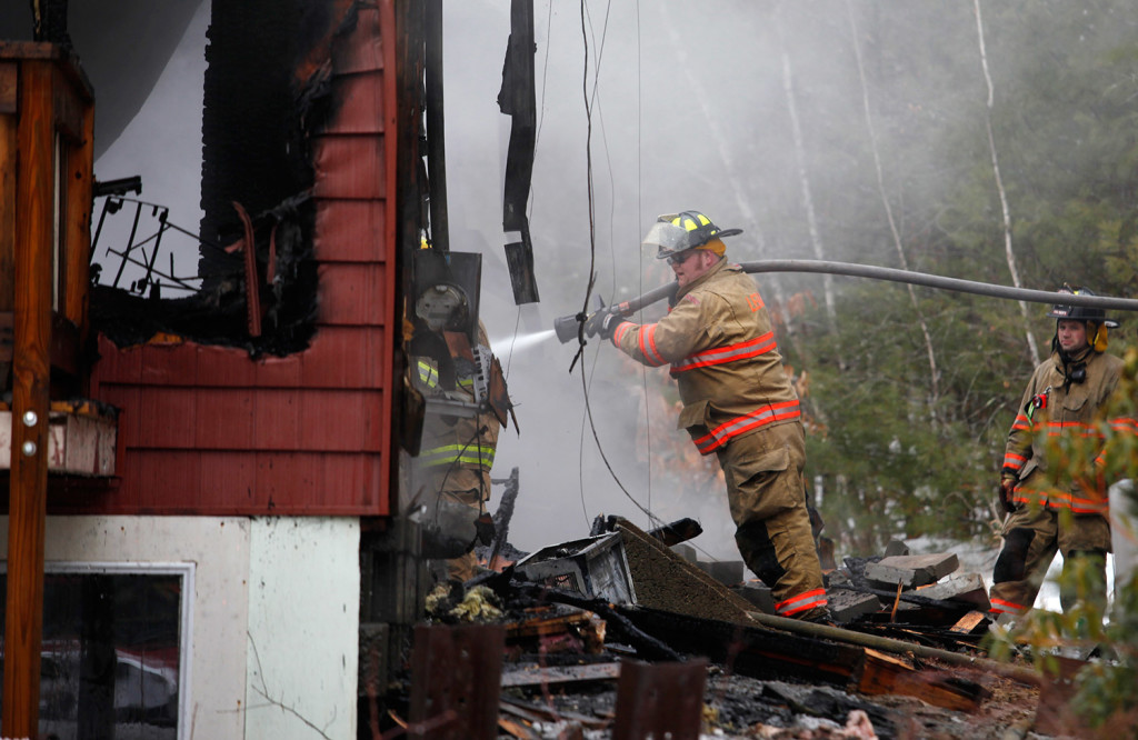 A firefighter sprays water onto the house that was destroyed by fire Wednesday in Lebanon. Joel Page/Staff Photographer