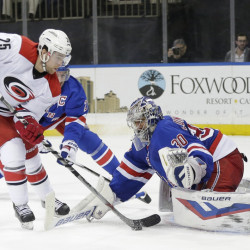 Carolina's' Chris Terry, left, controls the puck in front of New York Rangers goalie Henrik Lundqvist during the third period of a 4-3 win by the Rangers at New York on Monday.
