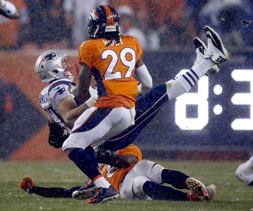 Rob Gronkowski is upended by Denver safeties Darian Stewart, on ground, and Bradley Roby. Later in Sunday night's game, Gronkowski was carted off the field.