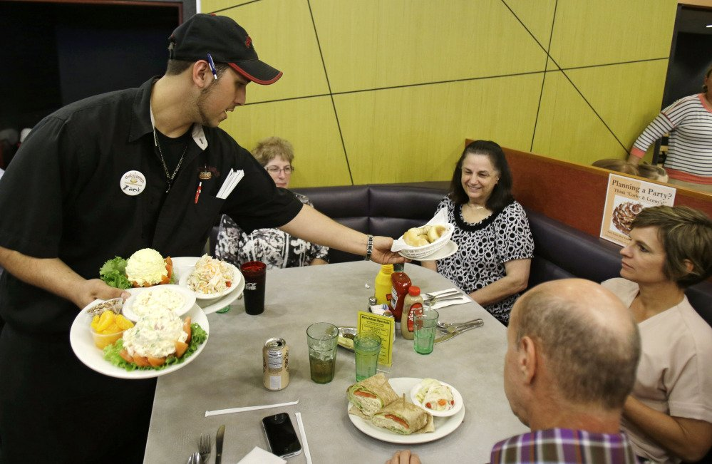 In this Friday, June 6, 2014, file photo, Zack Adams delivers food to customers at Corky & Lenny's Restaurant & Deli in Woodmere Village, Ohio.