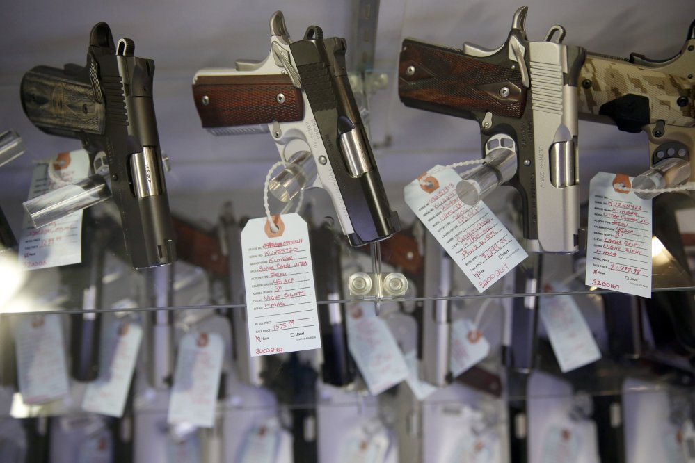 Handguns sit in a glass display case in Bridgeton, Mo., in November 2015.