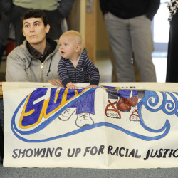 Christine Baglieri, with Showing Up for Racial Justice, Central Maine Chapter, awaits her turn to speak as she sits with a friend's child, Jackson, behind a banner at a rally to stand together against institutional racism, at the Woodbury Center at the University of Southern Maine on Wednesday.