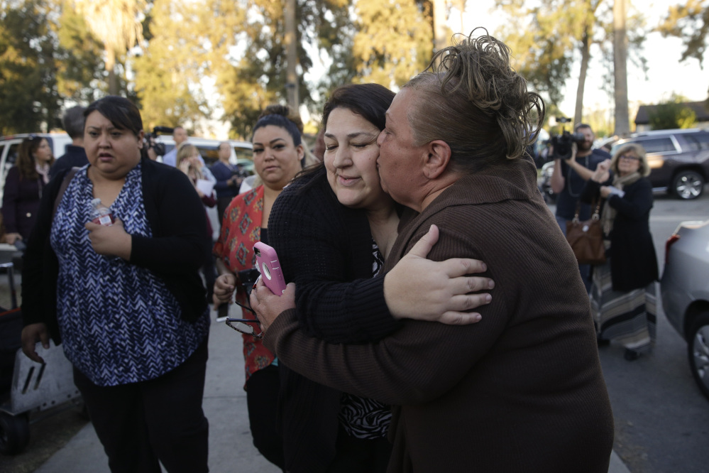 A woman who declined to give her name kisses her sister, center, who survived Wednesday's shooting rampage in San Bernardino, Calif. More than 600 people work at the Inland Regional Center.