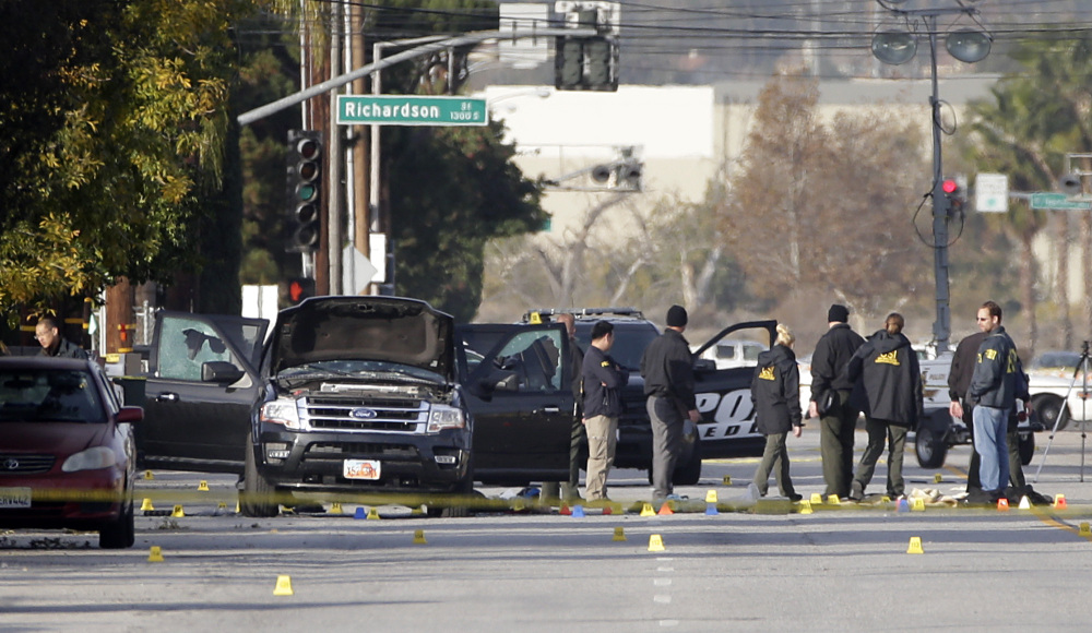 Investigators on Thursday gather around a black SUV that was involved in Wednesday's police shootout with suspects in the San Bernardino, California, massacre.
