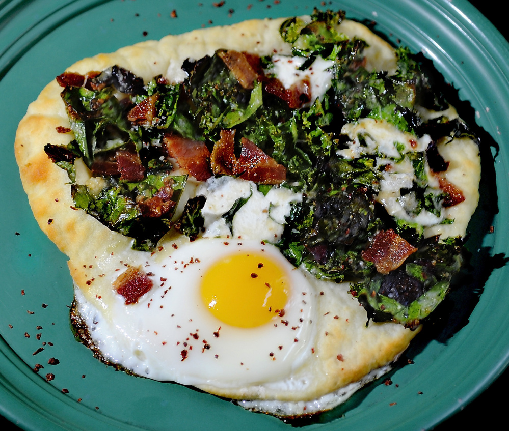 A two-ingredient flatbread forms the base for an Egg-in-the-Hole Pizza with bacon, greens and pepper. Gordon Chibroski/Staff Photographer
