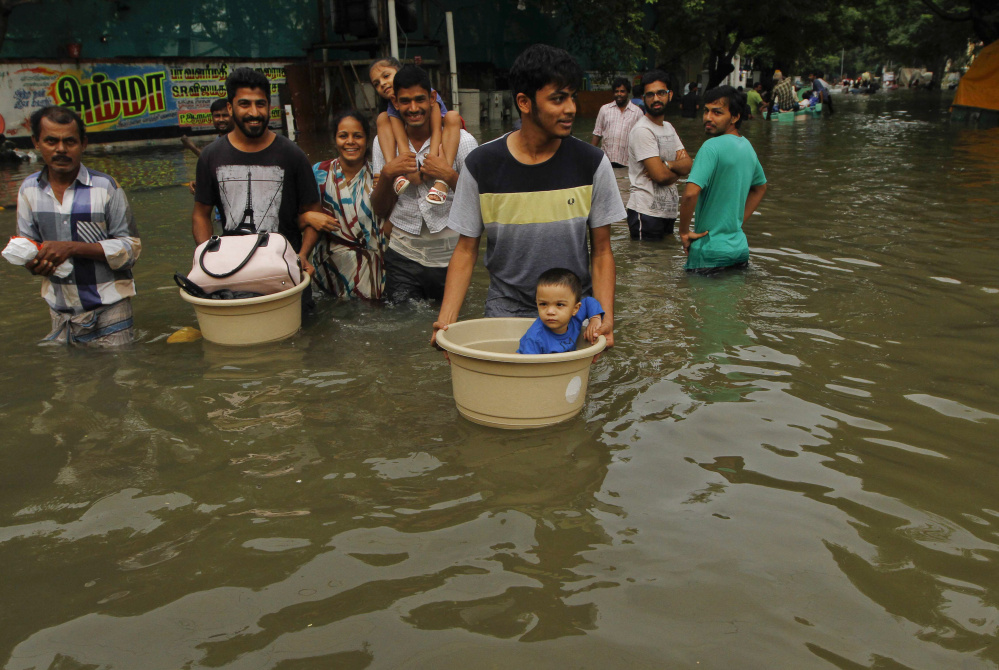 The Associated Press People with their children wade through floodwaters Thursday in Chennai, India.