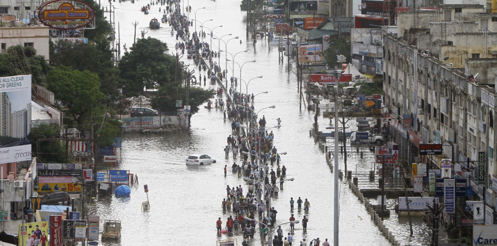 People walk through a flooded street Thursday in Chennai, the capital of the southern Indian state of Tamil Nadu.