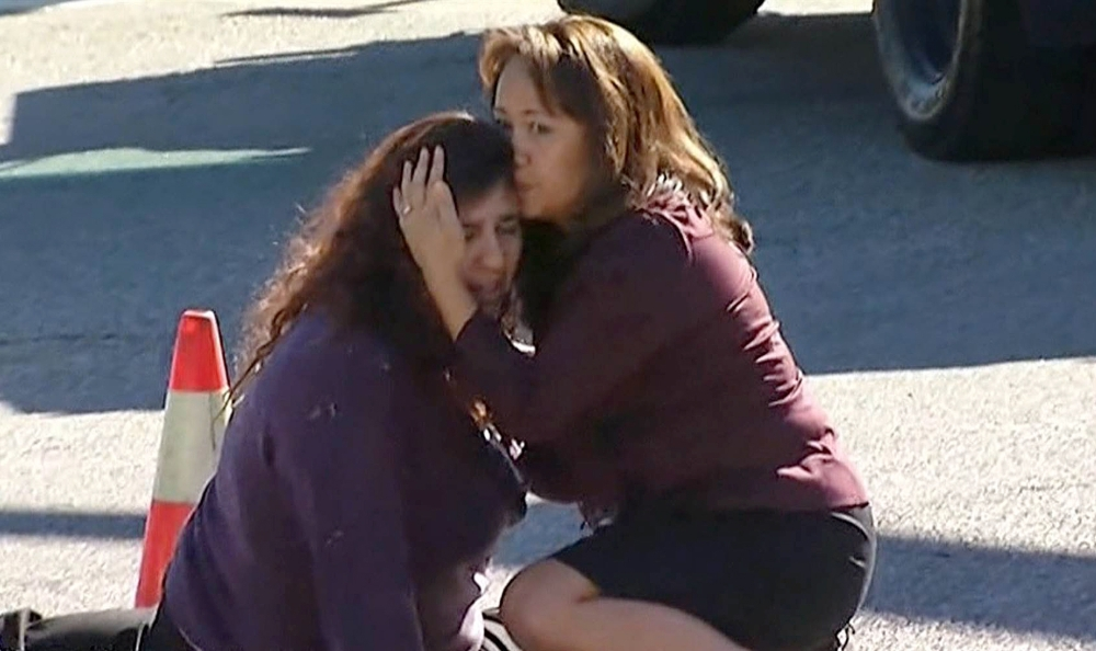 Two women comfort each other near the scene of a shooting outside a social services center in San Bernardino, Calif., where two gunmen opened fire, killing 14 people Wednesday. Authorities are still trying to determine a motive.