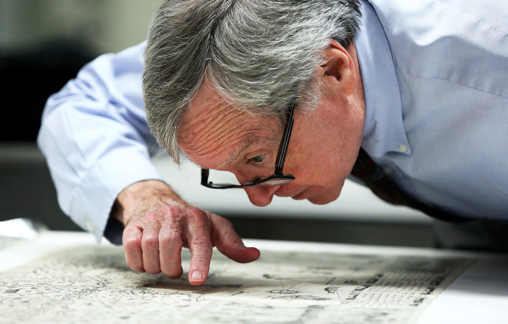 Boston Public Library curator of maps Ronald Grim, who helped reclaim a centuries-old map that was stolen from the library, examines the map Thursday in Boston.