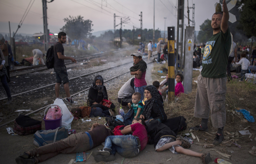 Syrian refugees wait near a Greek rail station in December 2015.