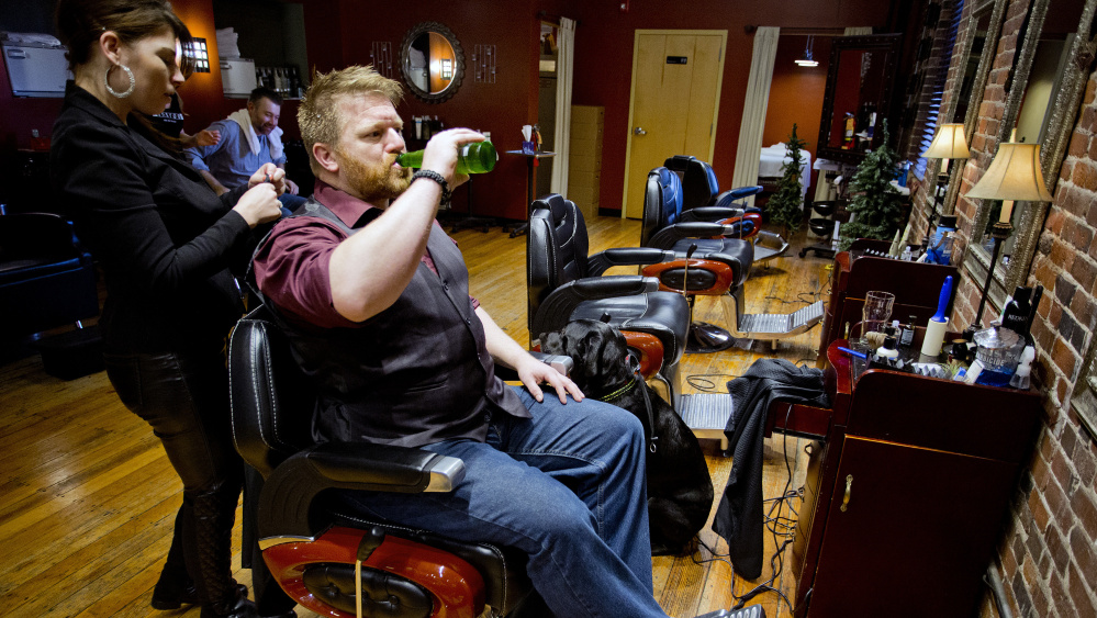 Fred Twombly drinks a beer with his dog, Milo, at his side as Christina Bailey prepares to cut his hair at Mensroom Salon & Lounge in Portland. Mensroom, which has operated in Portland for more than a decade, is part of a business segment that seems to be growing in popularity: a place to get your hair cut while having a beer and maybe shooting a round of pool.