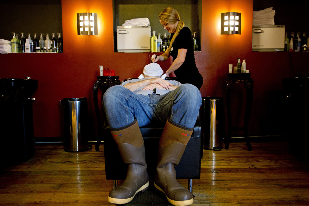 Allen Baldwin of Portland receives a hot towel treatment from Alicia Newcomb before his haircut at Mensroom Salon & Lounge in Portland. Owner June Juliano started the salon because she saw how uncomfortable men were at a woman's salon. Gabe Souza/Staff Photographer
