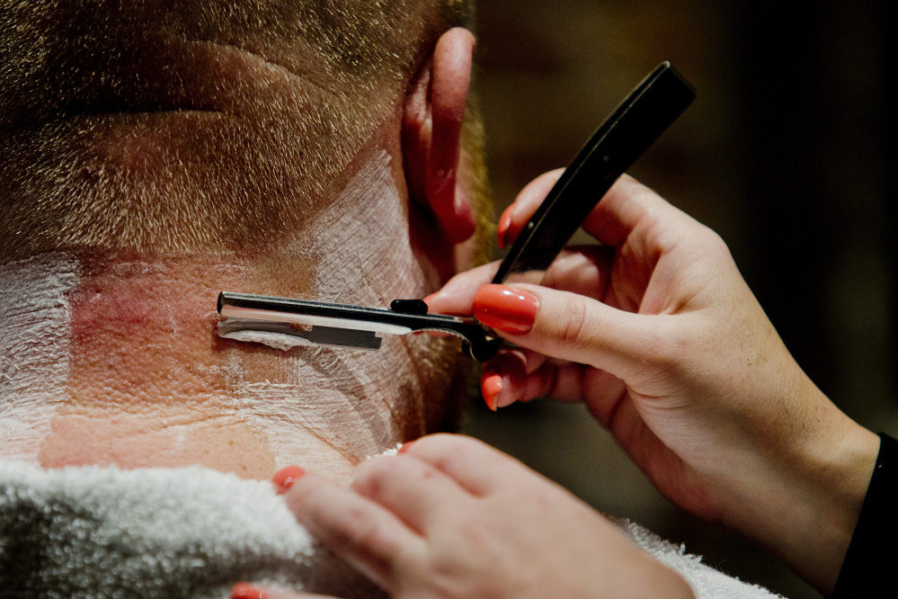 Men get a straight razor shave after their haircut at the Mensroom. Gabe Souza/Staff Photographer
