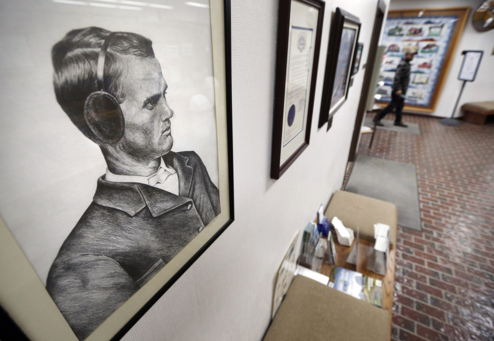 """A portrait of earmuffs inventor Chester Greenwood hangs at the municipal offices in his hometown of Farmington. In 1873 at age 15, Greenwood made his first pair of """"ear protectors"""" with help from his grandmother after he returned from a cold day of ice skating."""