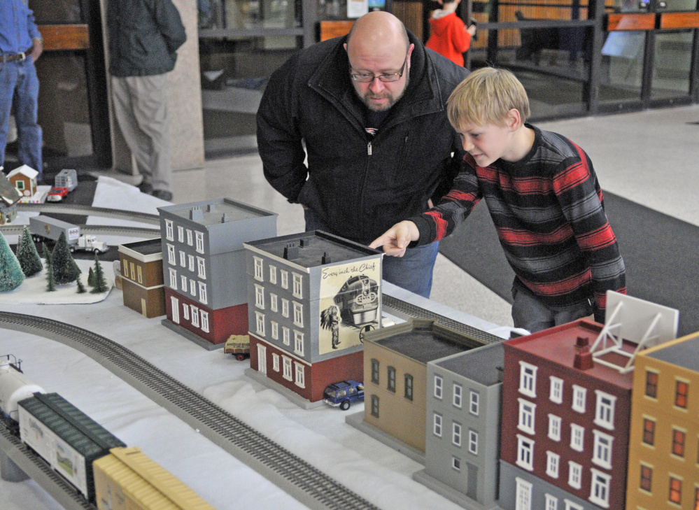 China residents Sean Boynton, left, and son Sam, 11, look at the model railroad displays Friday in the atrium of the Cultural Building, which houses the Maine State Museum, in Augusta.