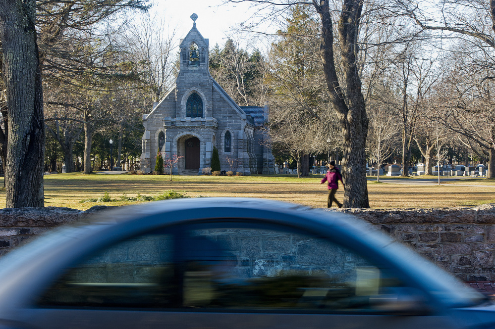 Barbara Ferguson of Portland walks through Evergreen Cemetery in Portland Saturday as a car whizzes past on Stevens Avenue. Gabe Souza/Staff Photographer