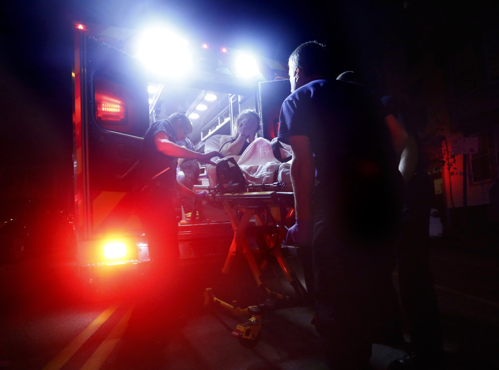 PORTLAND, ME - AUGUST 12: Portland paramedics respond to a call of a heroin overdose on Congress Street near the intersection of India Street. The 29-year-old woman was found unconscious by a passerby after she had injected herself with a quarter gram of heroin. Derek Davis/Staff Photographer