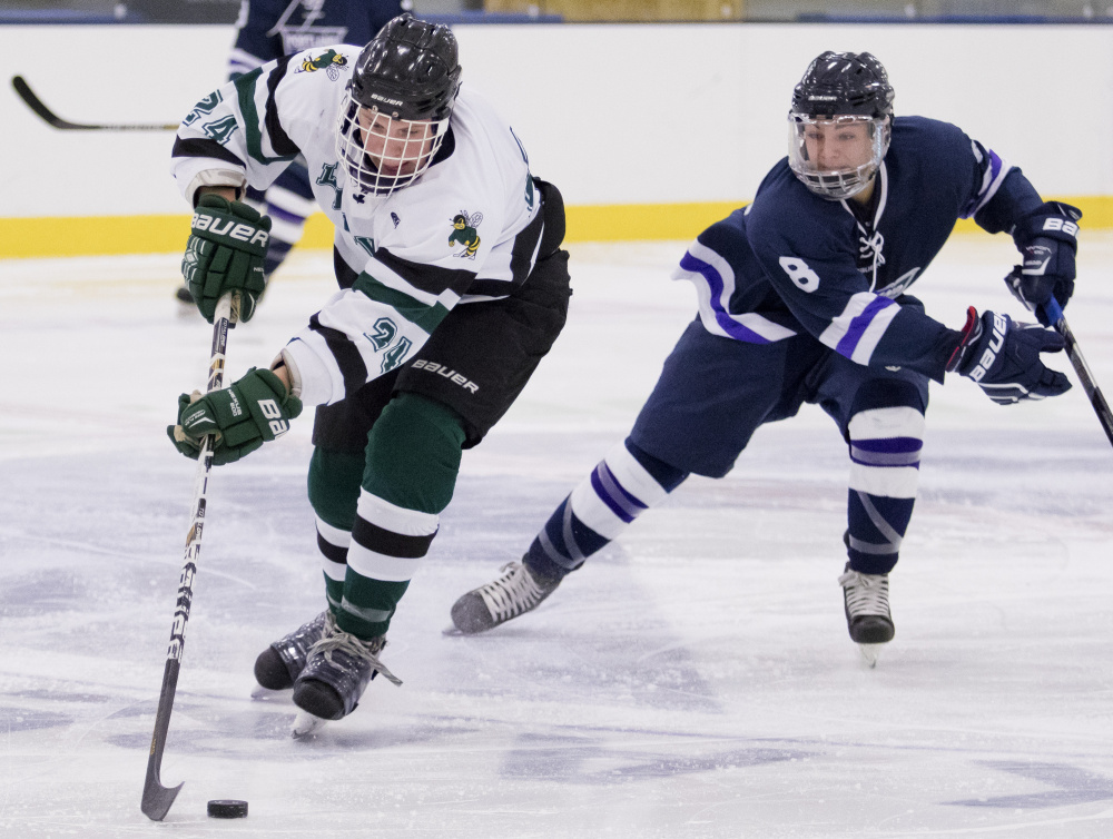 Leavitt's Lucas Perry skates up ice with Portland/Deering's Giovanni Ruotolo in pursuit during Saturday's ame at the Norway Savings Bank Arena in Auburn Photo by Gabe Souza/Staff Photographer