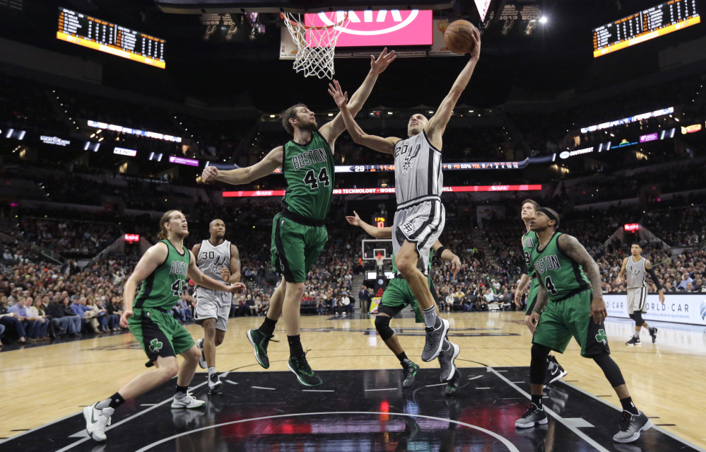 San Antonio Spurs guard Manu Ginobili (20) drives to the basket against Boston Celtics center Tyler Zeller (44) during the first half of Saturay's game in San Antonio.