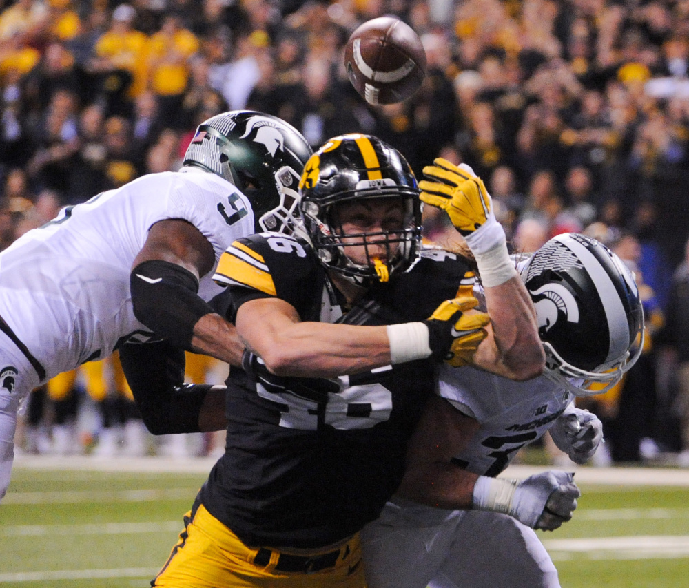 George Kittle of Iowa is unable to catch a pass in the end zone Saturday night as Montae Nicholson, left, and Riley Bullough of Michigan State defend in the second quarter of Michigan State's 13-10 victory in the Big Ten championship game at Indianapolis.
