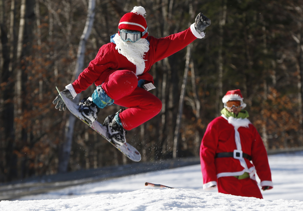 Snowboarder Jaden Bao, 12, of South Portland, catches some air while participating in Santa Sunday, the 16th annual charity fundraising event at the Sunday River ski resort, on Sunday in Newry.