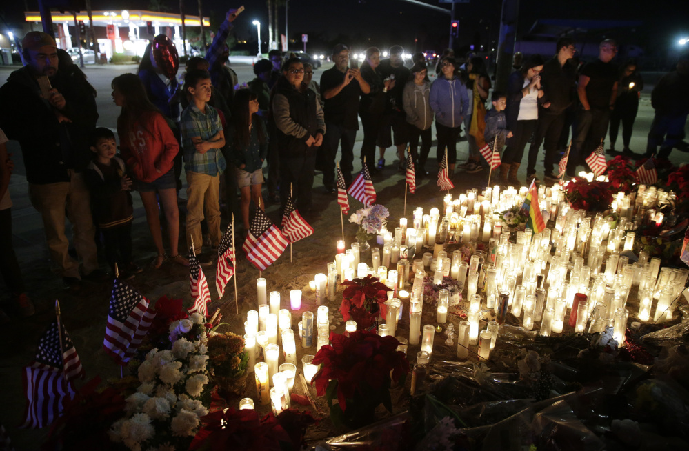 People pay respects to last week's shooting victims Sunday evening at a makeshift memorial in San Bernardino, Calif. Also Sunday, authorities searched the home of a of a man suspected of providing shooter Syed Rizwan Farook with guns.